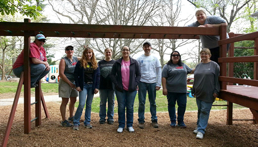 "Dansko Volunteers Hit the Road During ""Footwear Cares"" Month of Service - A team of Dansko employees pose after updating a playground for a local day care"