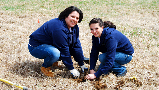 "Dansko Volunteers Hit the Road During ""Footwear Cares"" Month of Service - Two Dansko volunteers smile while taking part in a tree plant"